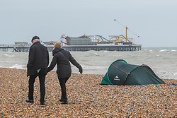 © Licensed to London News Pictures. 11/01/2020. Brighton, UK. A rough-sleepers tent is pitched up on the beach in Brighton and Hove as as powerful waves are hitting the coastline grey clouds hang over the seaside resort. Photo credit: Hugo Michiels/LNP