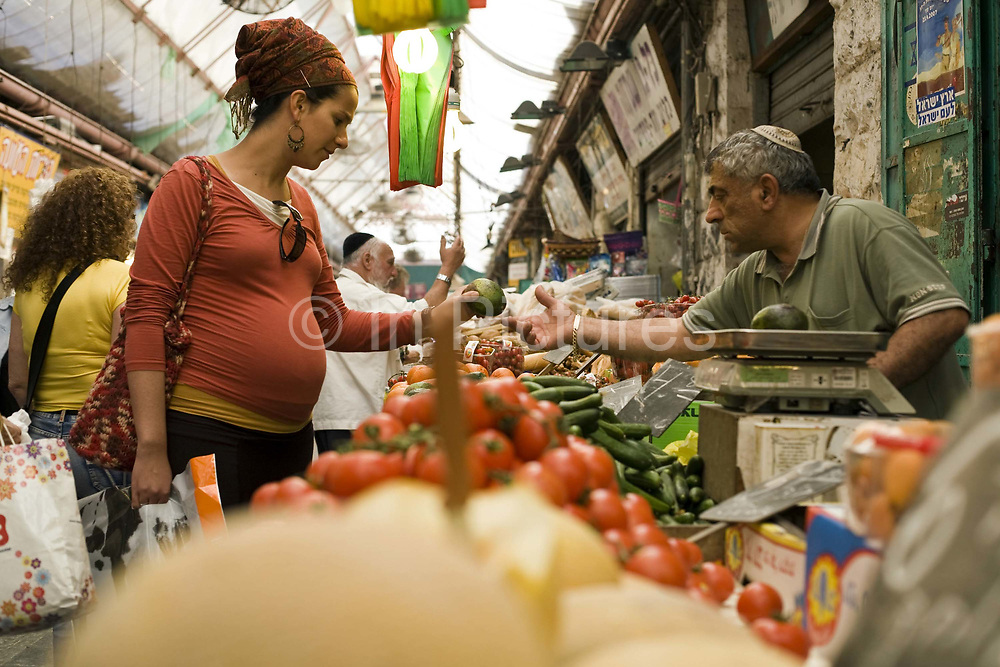 A man buys vegetable on a stall in the Mahane Yahuda Market, Jerusalem, Israel