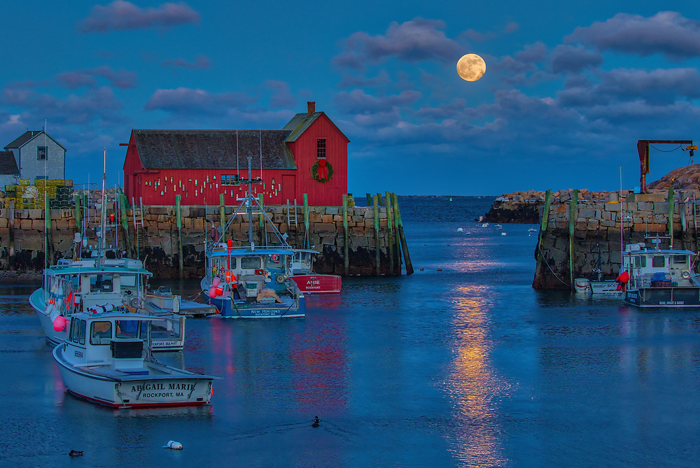 This New England photography image of Rockport Motif #1 with a rising full moon is available as museum quality photography prints, canvas prints, acrylic prints, wood prints or metal prints. Prints may be framed and matted to the individual liking and decorating needs: <br /> <br /> https://juergen-roth.pixels.com/featured/rising-full-moon-over-massachusetts-rockport-harbor-village-juergen-roth.html<br /> <br /> New England harbor scenery photography of this famous red fishing shack in Rockport, MA on Cape Ann was photographed on a bitter cold night in January. The historic landmark is known throughout New England as Motif #1, so called because it is the most often painted building in America.<br /> <br /> Good light and happy photo making!<br /> <br /> My best,<br /> <br /> Juergen<br /> Licensing: http://www.rothgalleries.com<br /> Photo Prints: http://fineartamerica.com/profiles/juergen-roth.html<br /> Photo Blog: http://whereintheworldisjuergen.blogspot.com<br /> Instagram: https://www.instagram.com/rothgalleries<br /> Twitter: https://twitter.com/naturefineart<br /> Facebook: https://www.facebook.com/naturefineart
