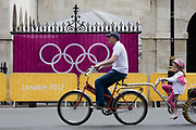 A father with a daughter in tow cycles past the IOC's Olympic logo brand of rings on a banner at Horse Guards in Whitehall during the London 2012 Olympics. Wrought iron railings are seen behind the banner at the sports venue hosting the volleyball in the centre of Westminster where governmental offices are located.