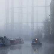 A work crew sails down the Regent's Canal on a misty morning, 27th of November 2020, Hackney, London, United Kingdom. The crew is from the Canal and River Trust and are on their way to King's Cross further up the canal. It is a misty and cold morning and no one else are on the canal, only the house boats moored along the canal. In the back ground are the now abandoned gas works with its structures disappearing in the mist.
