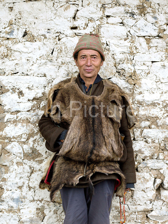 On an 'auspicious day', a Brokpa man wearing a sleeveless deer skin vest over his 'gho' a traditional long sleeved woollen tunic made from yak wool stands outside the temple in Merak, Eastern Bhutan.