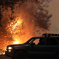 A motorist fleeing the CZU August Lightning Complex turns around after finding Pine Flat Road in Bonny Doon, California blocked by flames on August 20, 2020.