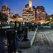 View of downtown Boston at night from Long Wharf. In the center of frame is the tall Marriot Custom House Hotel clock tower. At left are some of the solid bollards along the wharf for ships to tie up to.