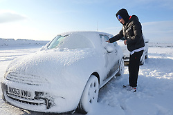 © Licensed to London News Pictures. <br /> 27/12/2014. <br /> <br /> Castleton, United Kingdom.<br /> <br /> A man clear snow from his car near The Lion Inn on the North Yorkshire Moors near Castleton after overnight snowfall caused disruption in some parts of the country.<br /> <br /> Photo credit : Ian Forsyth/LNP