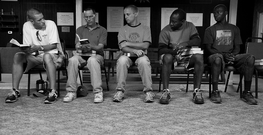 Rubio L. reads from a christian based book during the mandatory Morning Devotional Meeting in a room that was once a horse stable. One by one each man read from a different book before sharing their thoughts on what they heard.