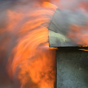 USA. Idaho. Canyon County. Caldwell. Fire Department practice burn on early 1940s era chicken coops