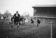 K C Briscoe of New Zealand, number 7, receives a pass from a loose scrum, with DJ Graham, number 9, on the right, ..Irish Rugby Football Union, Ireland v New Zealand, Tour Match, Landsdowne Road, Dublin, Ireland, Saturday 7th December, 1963,.7.12.1963, 12.7.1963,..Referee- H Keenen, Rugby Football Union, ..Score- Ireland 5 - 6 New Zealand, ..Irish Team, ..T J Kiernan, Wearing number 15 Irish jersey, Full Back, Cork Constitution Rugby Football Club, Cork, Ireland,..J Fortune, Wearing number 14 Irish jersey, Right Wing, Clontarf Rugby Football Club, Dublin, Ireland,..P J Casey, Wearing number 13 Irish jersey, Right Centre, University College Dublin Rugby Football Club, Dublin, Ireland, ..J C Walsh,  Wearing number 12 Irish jersey, Left Centre, University college Cork Football Club, Cork, Ireland,..A T A Duggan, Wearing number 11 Irish jersey, Left Wing, Landsdowne Rugby Football Club, Dublin, Ireland,..M A English, Wearing number 10 Irish jersey, Stand Off, Landsdowne Rugby Football Club, Dublin, Ireland, ..J C Kelly, Wearing number 9 Irish jersey, Captain of the Irish team, Scrum Half, University College Dublin Rugby Football Club, Dublin, Ireland,..P J Dwyer, Wearing number 1 Irish jersey, Forward, University College Dublin Rugby Football Club, Dublin, Ireland, ..A R Dawson, Wearing number 2 Irish jersey, Forward, Wanderers Rugby Football Club, Dublin, Ireland, ..R J McLoughlin, Wearing number 3 Irish jersey, Forward, Gosforth Rugby Football Club, Newcastle, England, ..W J McBride, Wearing number 4 Irish jersey, Forward, Ballymena Rugby Football Club, Antrim, Northern Ireland,..W A Mulcahy, Wearing number 5 Irish jersey, Forward, Bective Rangers Rugby Football Club, Dublin, Ireland,  ..E P McGuire, Wearing number 6 Irish jersey, Forward, University college Galway Football Club, Galway, Ireland,  ..P J A O' Sullivan, Wearing  Number 8 Irish jersey, Forward, Galwegians Rugby Football Club, Galway, Ireland,..N A Murphy, Wearing number 7 Irish jersey, Forward, Cork Cons