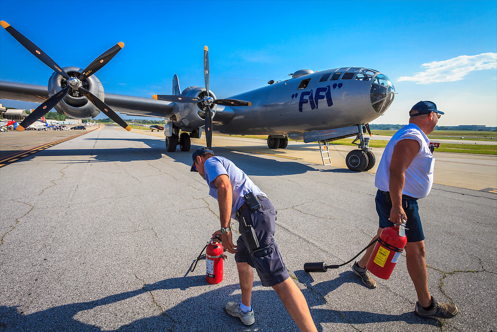 """Ground crew stand-by with fire extinguishers as """"Fifi"""", the Commemorative Air Force's B-29 Superfortress, prepares to start her engines."""