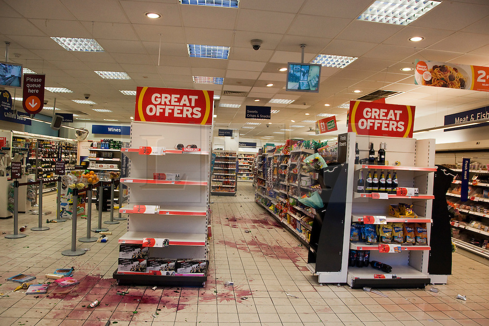 © Licensed to London News Pictures. 09/08/2011. London, Camden Town, UK. Damaged shops and premises after a night of rioting in Camden Town, London. Looted Sainsbury's store in Chalk Farm Road. Photo credit: Bettina Strenske/LNP