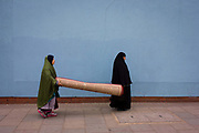 Two muslim women carry a heavy carpet along street at Elephant & Castle in Southwark, south London. Walking along a blue wall, the ladies make their way from a nearby shop on the Walworth Road to their home nearby. Both looking to the front they progress along the street with their domestic purchase.