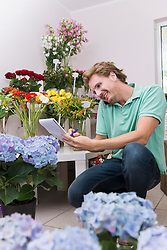 Mid adult man taking order of flowers, smiling
