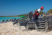 Bahamian lifeguard puts away beach loungers after most of the cruise ship passengers have returned to the ship.