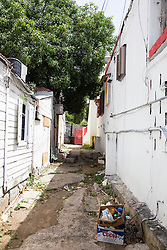 Alleyways allowed townspeople easy access between small buildings clustered close together.  The Virgin Islands Economic Development Association Enterprise & Commercial Zone Commission hosts a historical tour through the Savan (Savanne) neighborhood.   St. Thomas, US Virgin Islands.  9 July 2015.  © Aisha-Zakiya Boyd