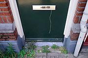 Nederland, Scheveningen, 20-6-2018Uit de voordeur van een huis  hangt een touwtje . Jan Terlouw constateerde dat deze verdwenen zijn omdat het vertrouwen in de samenleving en de eigen buurt, de buurtcohesie, verdwenen is .Foto: Flip Franssen