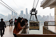 People stand on a platform as they wait to board a cable car across the Yangtze River in Chongqing, China, on Thursday, April 14, 2016. The municipality of 30 million people saw state-led development approach fueled the fastest pace nationwide, with President Xi Jinping praising policy innovations that have included subsidized housing and relaxed residency rules that encourage labor mobility.