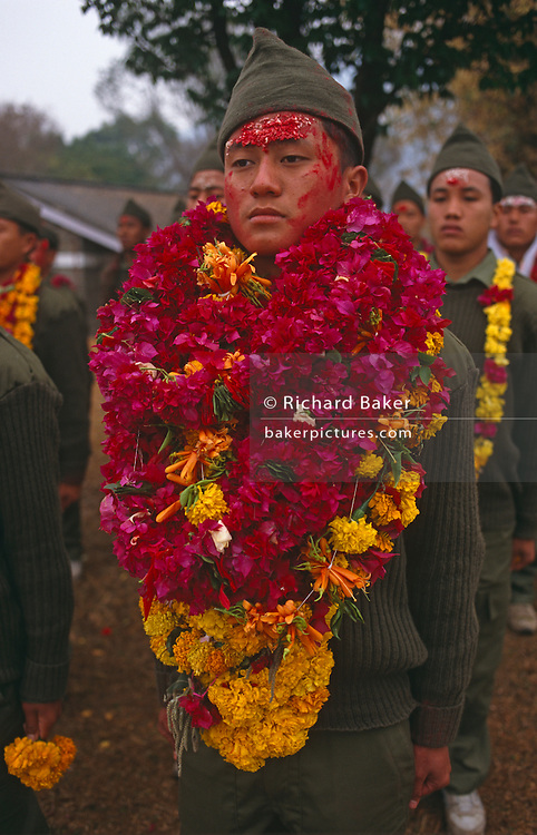 A newly-recruited Nepali boy is about to leave his homeland for the UK, where the British army is to make him a fully-trained soldier in the Gurkha Regiment. Daubed with saffron and paint, the sign of good luck on a journey to come, he stands with absolute pride with garlands of fresh flowers draped around his neck by well-wishing relatives before they wave good bye to their son or brother for his two years absence away from home. Some 60,000 young Nepalese boys aged between 17 - 22 (or 25 for those educated enough to become clerks or communications specialists) report to designated recruiting stations in the hills each November, most living from altitudes ranging from 4,000 - 12,000 feet. After initial selection, 7,000 are accepted for further tests from which 700 are sent down here to Pokhara in the shadow of the Himalayas. Only 160 of the best boys succeed in the flight to the UK. The Gurkhas training wing in Nepal has been supplying youth for the British army since the Indian Mutiny of 1857.