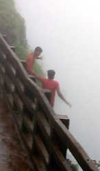 August 1, 2017 - Maharashtra, India - Video screen grab of moment the two fall from cliff. Imran Garadi (26) and Pratap Rathod (21), are seen standing on the edge of a precipice, beyond the fence at Amboli Ghat, a popular picnic spot in Maharashtra, India.....Imran, 26 and Pratap, 21, along with five other men went to the popular picnic spot Amboli Ghat to enjoy their evening. The two men went their separate ways from the rest of the group.  They were in a drunken state with bottles in their hands, they climbed over the fence and fell into the deep 2000ft valley. Two rescue teams have been searching for the bodies but they are yet to be recovered. (Credit Image: © Cover Asia Press/Cover Asia via ZUMA Press)