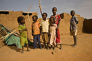 Young children play in the barren dust of the 4 sq km Abu Shouk refugee camp which is (disputedly) home to 38,000 displaced persons and families on the outskirts of the front-line town of Al Fasher (also spelled, Al-Fashir) in north Darfur. .