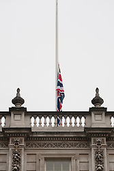 © licensed to London News Pictures. London, UK 06/07/2012. An Union Jack flag being taken down before a rainbow flag goes up above The Cabinet Office today in celebration of Worldpride. Photo credit: Tolga Akmen/LNP