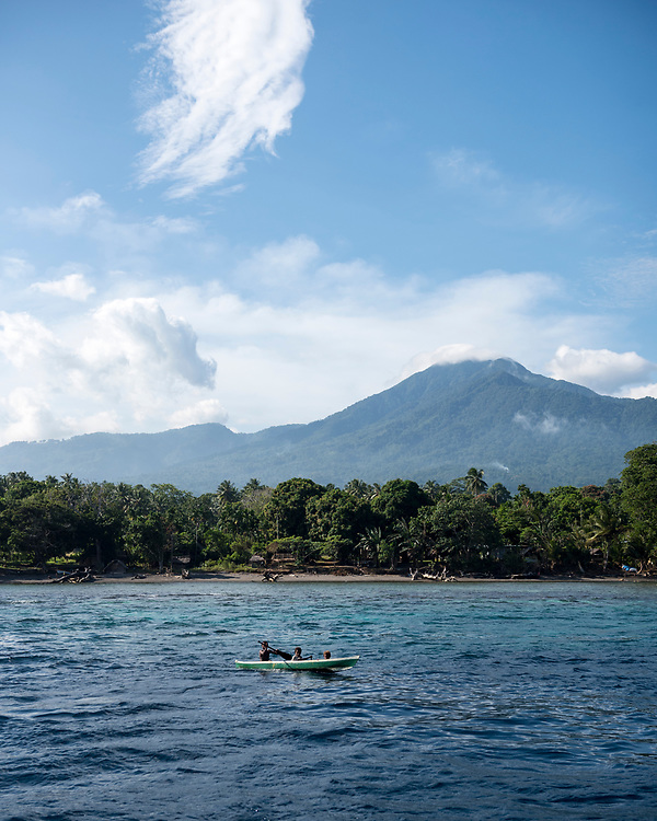 Three children paddle a canoe off the coast of Karkar Island in Madang Province, Papua New Guinea. The island's peak is a dormant volcano.