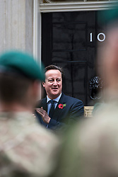 © London News Pictures. 10/11/2012. London, UK. British Prime Minister David Cameron talking to Royal Marines from Commando 999 (Royal Marines who serve with the UK emergency services)  outside number 10 Downing Street before the Marines take part in a speed march around London in record time to raise funds for wounded service personnel. The charity event takes place on Remembrance weekend.  Photo credit: Ben Cawthra/LNP