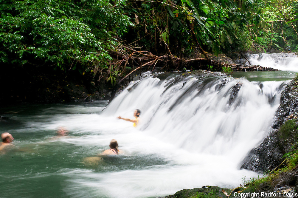 Waterfall and swimmers in Costa Rica rain forest