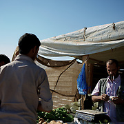 August 08, 2013 - Zaatari, Jordan: Syrian refugees buy goods at a vegetable shops in Zaatari refugee camp in northern Jordan. The stall is located on a street that aid workers have nicknamed the Champs Elysees, due to the hundreds of shops and businesses. Zaatari camp, home to more than 120,000 people who in the past year have fled the conflict in Syria, become the fourth largest city in Jordan and the world's second largest refugee camp behind Dadaab in eastern Kenya. Most of its residents came from Daraa, a city about 30Km away in Syria, rich with businessmen thanks to a long history of cross-border trade with Jordan. (Paulo Nunes dos Santos/Al Jazeera)