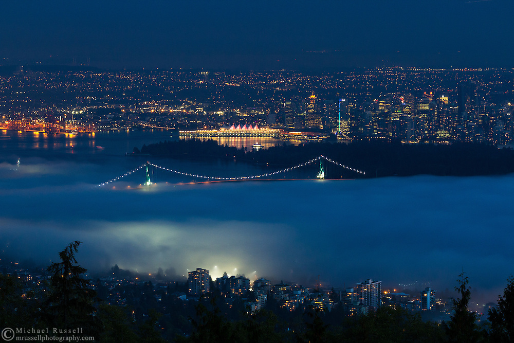 View of West Vancouver, the Lions Gate Bridge, Stanley Park and downtown Vancouver as the fog rolls in from English Bay to Burrard Inlet.  Photographed from the Cypress Lookout at Cypress Provincial Park in West Vancouver, British Columbia, Canada