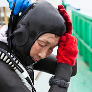 Inaba-san putting on her wetsuit and other gear to go into the ocean
