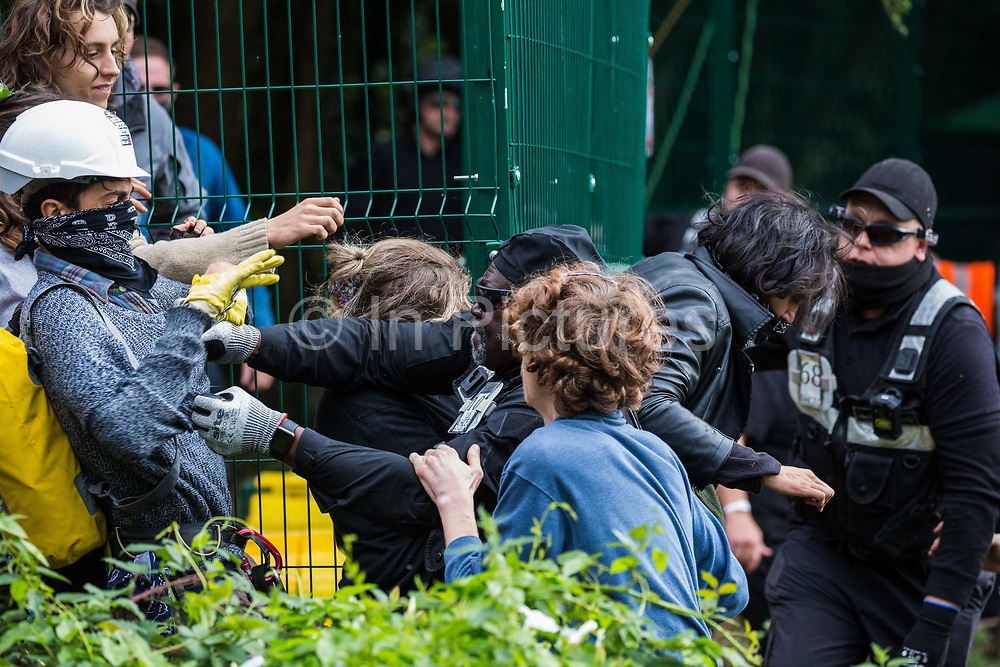 A National Eviction Team enforcement agent grasps the clothing of an HS2 Rebellion activist during direct action by anti-HS2 activists to prevent or delay tree cutting in conjunction with the high-speed rail link in Denham Country Park on 7 September 2020 in Denham, United Kingdom. Anti-HS2 activists continue to campaign and take direct action against the controversial £106bn project for which the construction phase was announced on 4th September from a series of protection camps based along the route of the line between London and Birmingham.