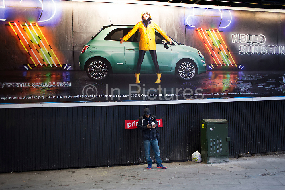 Advertising billboard mimics the real life underneath it, as a man stands texting underneath the car advert, which shows a person of a similar size and position. London, UK.