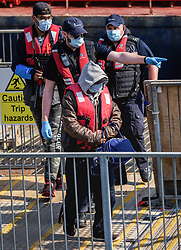 © Licensed to London News Pictures. 20/07/2021. Dover, UK. A migrant is escorted by Border Force officers as he is brought ashore at Dover Harbour in Kent after crossing the English Channel. It is being reported that at least 430 migrants crossed the English Channel to the UK on Monday, a new single day record. Photo credit: Stuart Brock/LNP