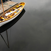 Small sailboat moored to floating dock in Camden Maine Harbor.
