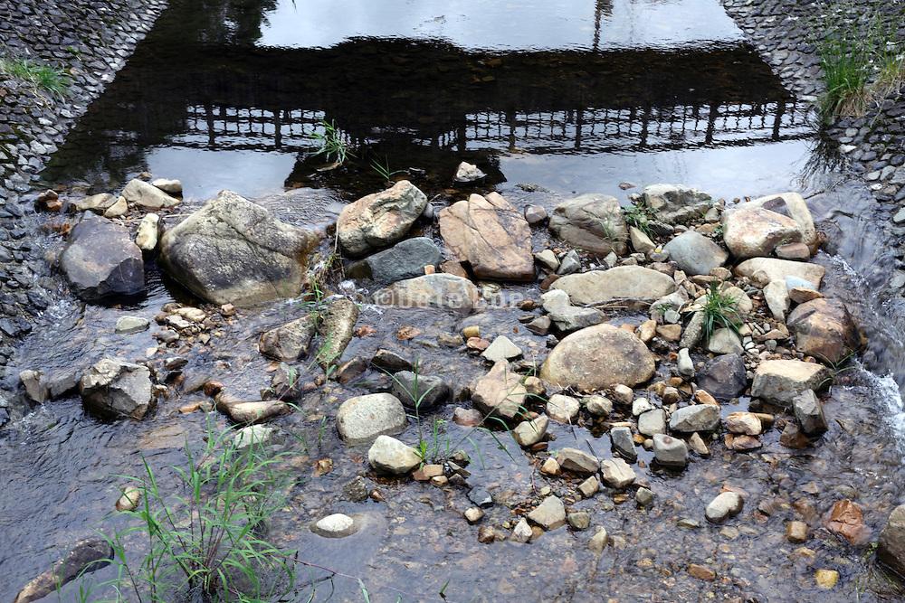 oriental bridge reflection in water with stones