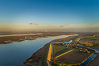 Aerial view of small village surrounding by agricultural land during scenic sunset, Netherlands.