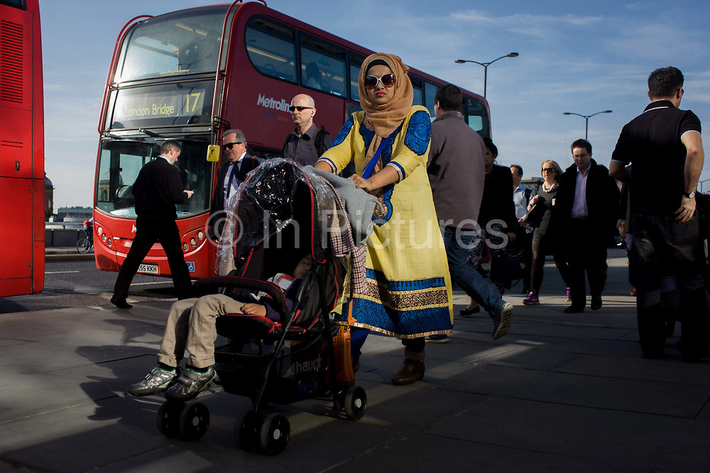Londoners cross southbound over London Bridge during the evening rush hour. A mother wearing stylish middle-eastern clothing pushes a child's buggy  followed by others walking away from the City of London. There has been a crossing over the Thames here since the Romans first forded the river in the early 1st Century with subsequent medieval and Victorian stone bridges becoming an important thoroughfare from the City on the north bank, to Southwark on the south where transport hubs such as the mainline station gets commuters to the suburbs and satellite towns.