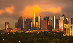 Dramatic lighting reflecting in buildings of downtown Houston, Texas skyline with an orange cloudy sky and trees in the foreground.