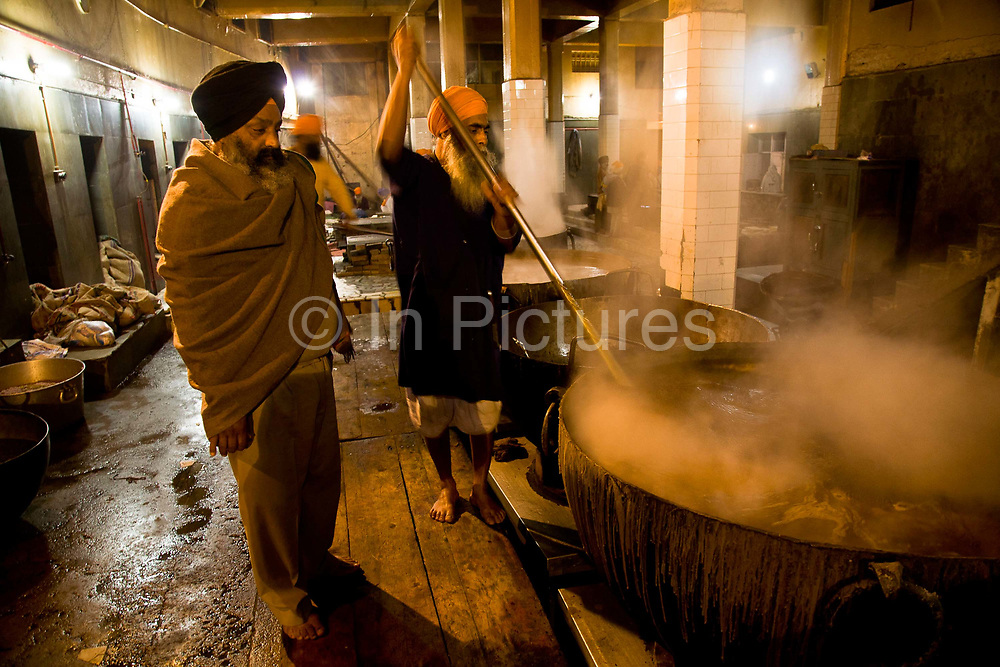 """Cooks preparing the midday meal in the Golden Temple's Langer (Kitchen) which serves up to 40.000 free meals a day. During the key Sikh religious festivities up to 500.000 meals can be served every day in Sikhisms holiest of places. Seen here stirring a vast vat of lentil soup. The Langar is manned by volunteers, given that according to their teachings """"charity"""" is central to their way of life and therefore offering your time, energy or funds is a way of saying thanks to God  through good deeds. Amritsar, Punjab, India."""