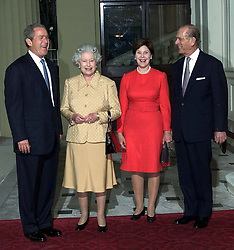 America's President Bush (left) is greeted by Britain's Queen Elizabeth II and the Duke of Edinbugh as he arrives out of the rain with his wife, Laura, at Buckingham Palace for lunch.    * The US president is on his first visit to the United Kingdom, before travelling on to the G8 summit in Genoa.