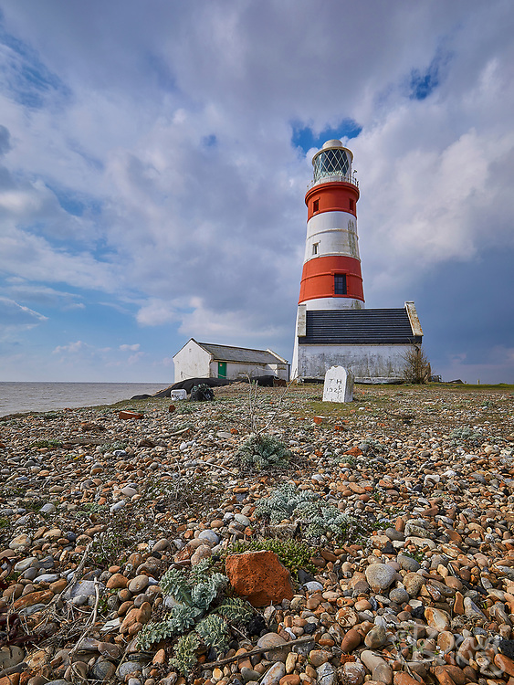 The old lighthouse on Orford Ness in Suffolk is in imminent danger of falling into the sea as the shingle beneath it is eroded. The little cottage seen on the left of the lighthouse here in April 2019 was destroyed in a storm in September 2019.