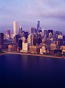 Aerial view from over Lake Michigan of early morning light illuminating the skyline of Chicago, Illinois.