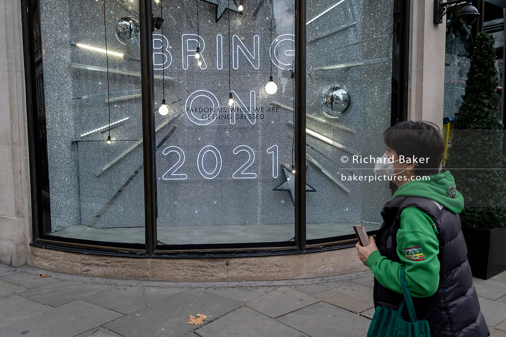 After a bleak year of Coronavirus pandemic misery, a shopper in Knightbridge walks past the temporary Christmas-themed Harvey Nichols window which urges Londoners to be optimistic for the coming year, on 12th November 2020, in London, England.