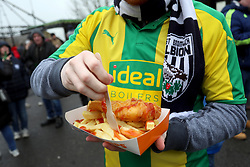A West Bromwich Albion fan grabs a bite to eat before the FA Cup fourth round match at the AMEX Stadium, Brighton.
