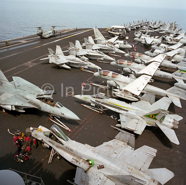 Up on the top deck of a US Navy aircraft carrier, parked F/A-18C Hornets and S-3 Vikings on the USS Harry S Truman during its deployment patrol of the no-fly zone at an unknown location in the Persian Gulf. Stacked together in tight formation to fit them all together during a daytime break in operations, the man bends into his task during the hottest time of day. The Truman is the largest and newest of the US Navy's fleet of new generation carriers, a 97,000 ton floating city with a crew of 5,137, 650 are women. The Iraqi no-fly zones (NFZs) were proclaimed by the United States, United Kingdom and France after the Gulf War of 1991 to protect humanitarian operations in northern Iraq and Shiite Muslims.