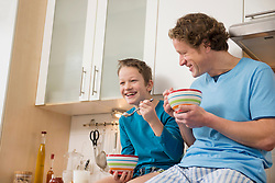 Father and son eating muesli in kitchen
