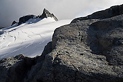 Rocky spires emerge from the crevassed Eldorado Glacier, North Cascades National Park, Washington.