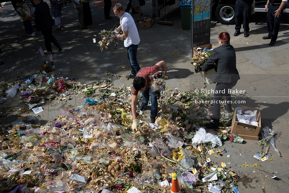 The faded flowers from the shrine dedicated to those killed in the London Bridge terrorist attack are collected from the pavement and respectfully disposed of, on 26th June 2017, in London, England.