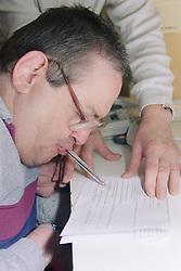 Man with Cerebral Palsy signing form with pen in mouth,