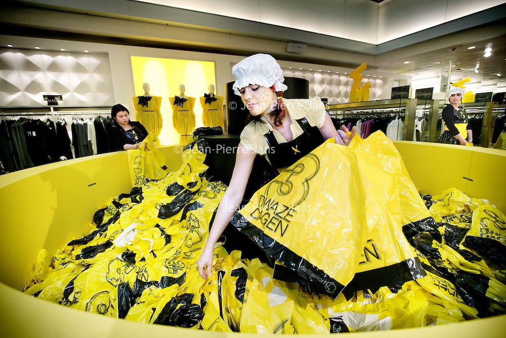 Nederland, Amsterdam , 1 oktober 2009..Verkleed personeel van warenhuis De Bijenkorf sorteert tijdens de eerste koopjes dag van de Drie dwaze Dagen plastic zakken met presentjes voor de bezoekers..Three Crazy Days, annual sale of the Bijenkorf store, promoting bargains.